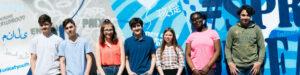Gruppe von Jugendlichen steht vor einer mit Graffitis besprühten Wand