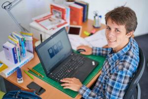 Jugendlicher sitzt vor Laptop mit dem Kompentenzcheck21-Tutorial und schaut in die Kamera
