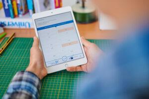 Hände halten Tablet, auf dem eine Aufgabe des Kompetenzcheck21 angezeigt wird
